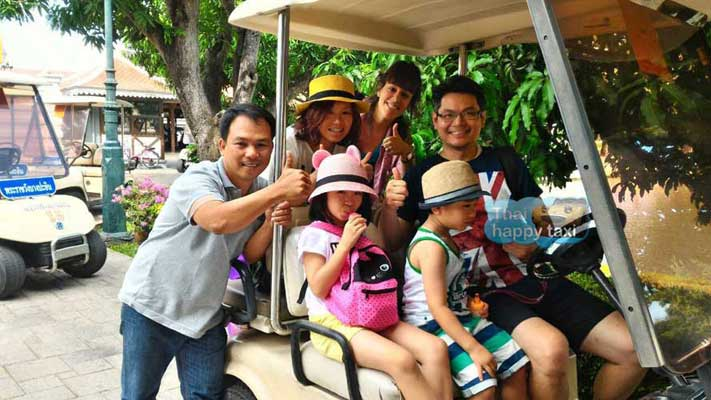 Thumps up all round. The nice family enjoys riding on a golf cart at Bang Pa In Palace, Ayutthaya.